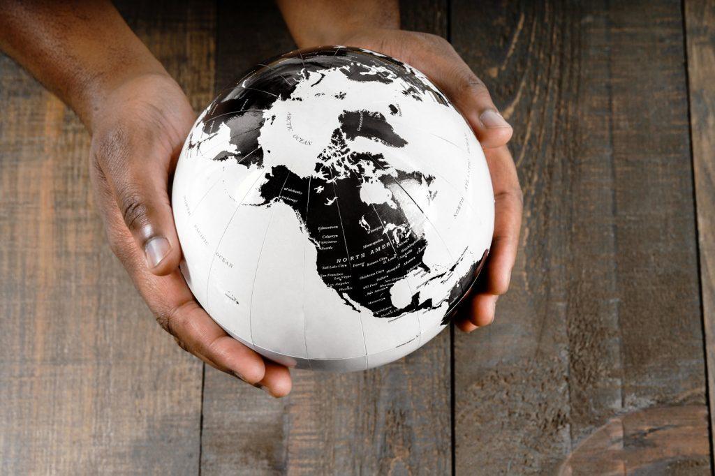 Mains tenant une mappemonde : carte du monde GPS ou pas